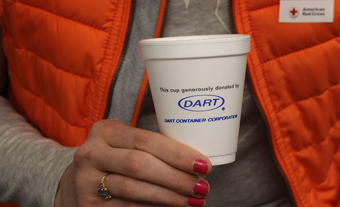 "Person holding Dart foam cup with text ""This cup generously donated by Dart Container Corporation"""